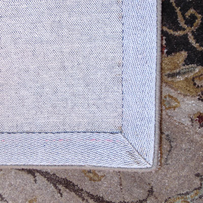 A Hand-tufted rug is identified by the backing on the backside